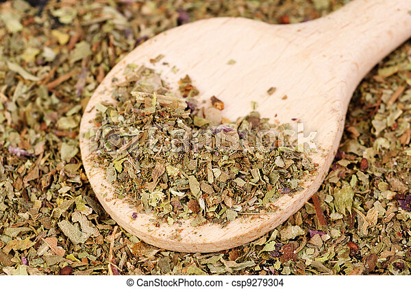 Pile of ground dried Basil (Sweet Basil) as background with wooden spoon. Used as a spice in culinary herb all over the world. The plant is also used in medicine. - csp9279304
