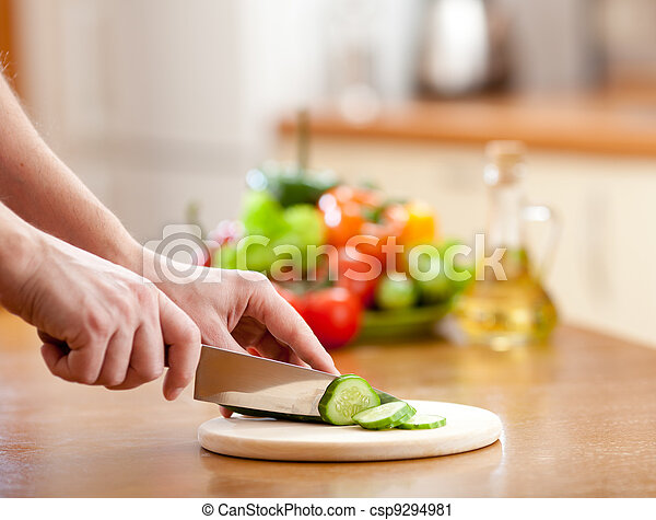 Male hands cutting of cucumer on hardboard and fresh vegetables on background - csp9294981