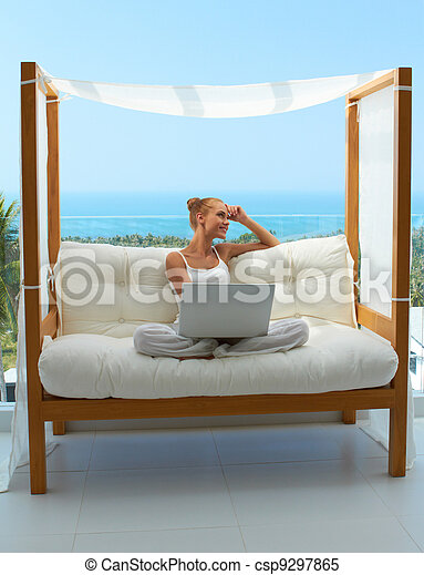 Woman with laptop on canopied seat - csp9297865