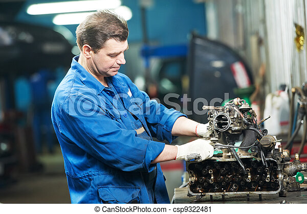 auto mechanic at repair work with engine - csp9322481