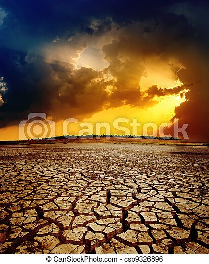 dramatic sunset over dry cracked earth - csp9326896