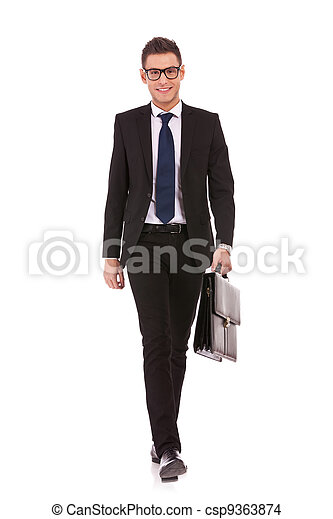 young business man carrying a suitcase, walking - csp9363874