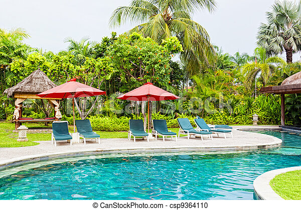 Chaise lounges at pool in hotel in tropics - csp9364110