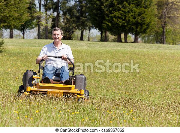 Senior man on zero turn lawn mower on turf - csp9367062