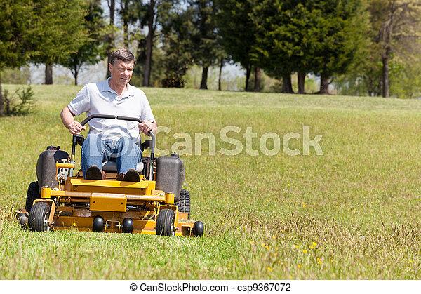 Senior man on zero turn lawn mower on turf - csp9367072
