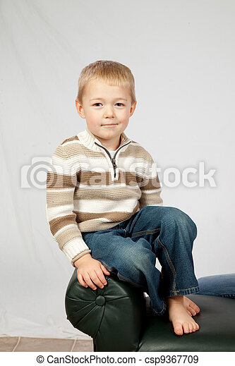 Blond boy sitting on bench end - csp9367709
