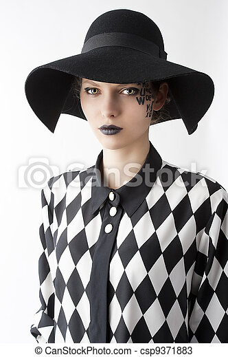 pretty and beautiful young lady with a creative make up made with letter on face and black hat and unusual shirt, she is in front of the camera and looks in to the lens with serious expression - csp9371883