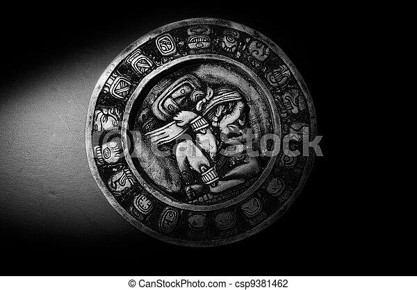 Carved Mayan calendar in dramatic light - csp9381462