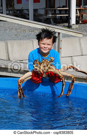 Norwegian youthful fisher with an alive king crab - csp9383805
