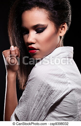 fashion portrait of beautiful american black female brunette girl model with bright makeup red lips in white shirt. Clean skin. Black background - csp9398032