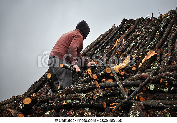 Man working on a charcoal pile - csp9399558