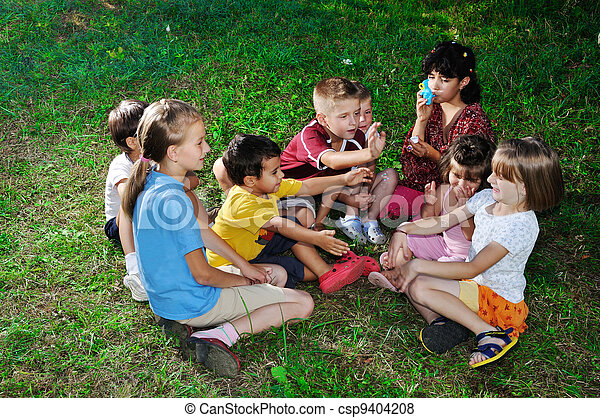 Photo of happy kids playing and blowing soap bubbles - csp9404208