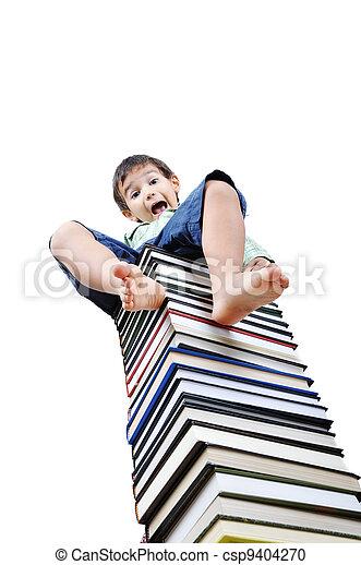 Cute little boy sitting on heap of textbooks - csp9404270