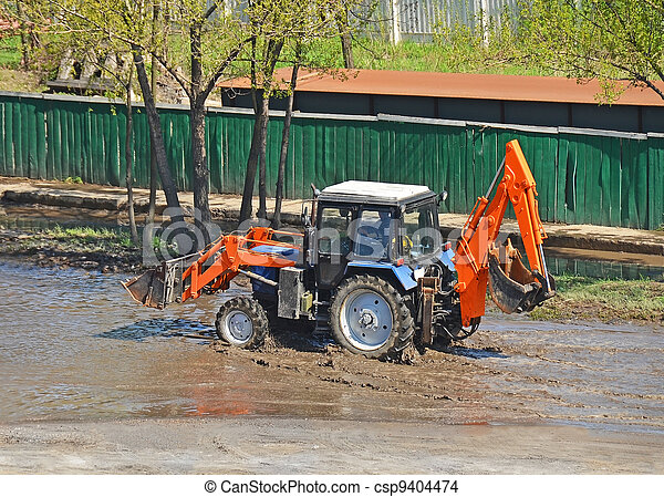 Tractor in a puddle on road construction site - csp9404474