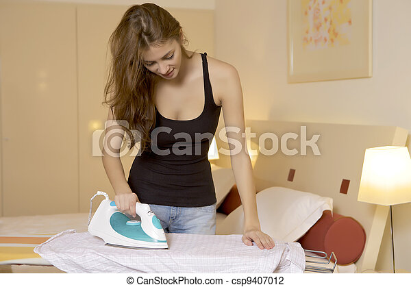 young woman ironing on ironing board - csp9407012