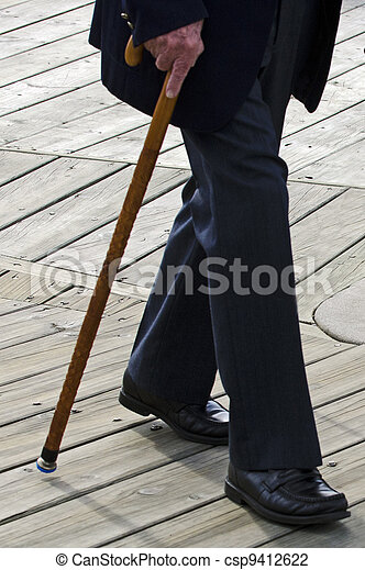 Profile of bottom half of an old man or elderly person walking with a wood cane stick wearing a dark suit. - csp9412622