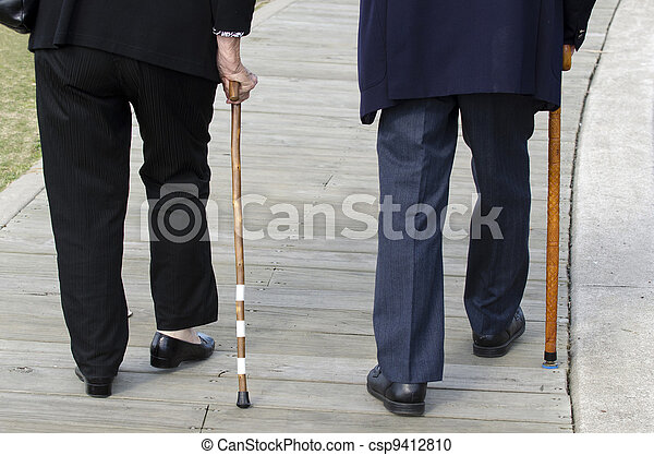 Bottom half of an elderly couple walking with a wood cane sticks wearing a dark suits. - csp9412810
