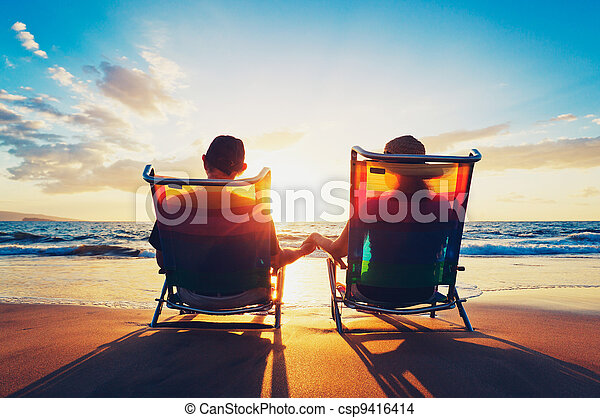 senior couple of old man and woman sitting on the beach watching sunset - csp9416414