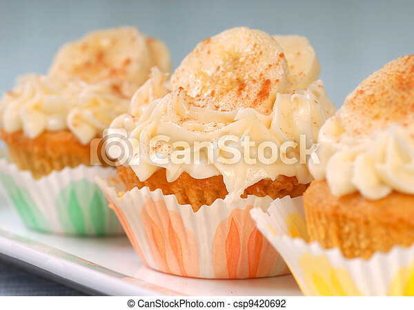 Vanilla cupcake with cream cheese frosting and sliced bananas - csp9420692