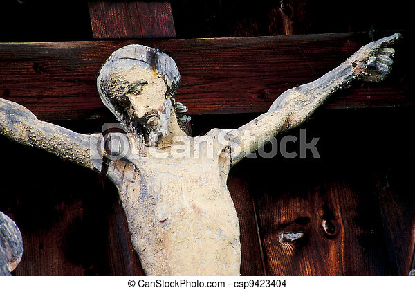 Weathered Jesus Christ figure nailed to the cross - csp9423404