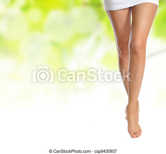 slender female legs making step over green - csp9430937