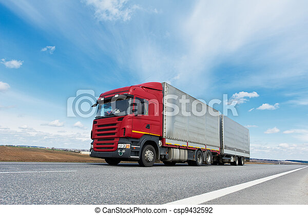 Red lorry with grey trailer over blue sky - csp9432592