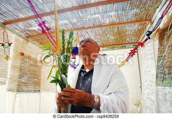 Praying in Sukkah for Jewish Holiday Sukkot - csp9438259