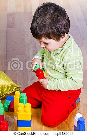 A happy little boy is building a colorful toy block tower - csp9439098