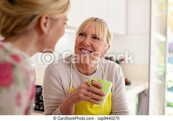 Mother and daughter talking, drinking coffee in kitchen - csp9440270