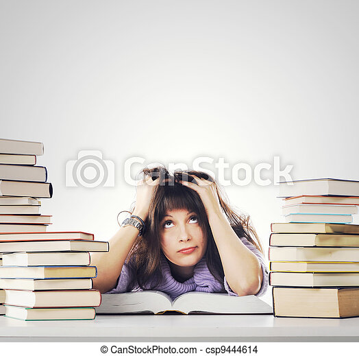 Tired of studies, young Woman is sitting on her desk with books  - csp9444614