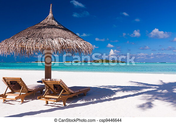 Chairs and umbrella on a beach with shadow from palm tree - csp9446644