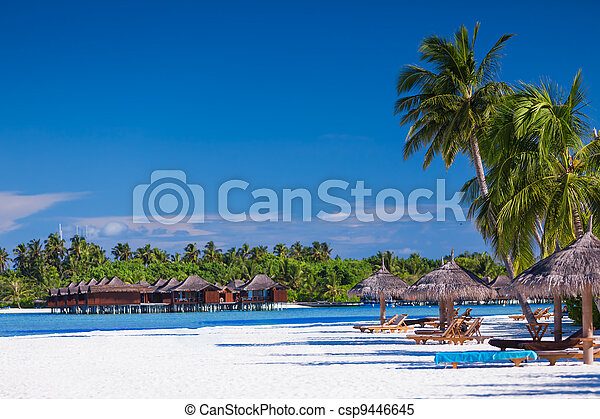 Palm trees over sandy tropical beach with villas over water - csp9446645