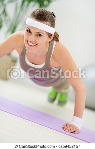 Happy fitness woman making push up exercise - csp9452157