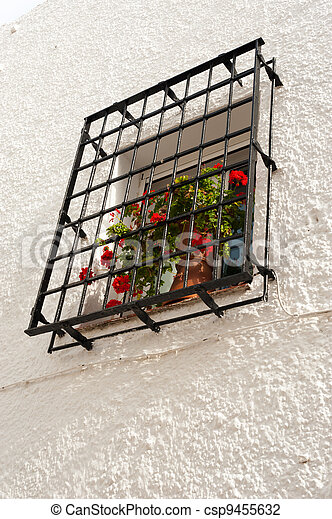 Traditional Andalusian window with red geraniums on the sill - csp9455632