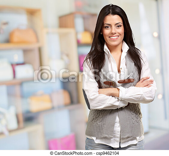 portrait of young woman with arms crossed against a fashion shop - csp9462104