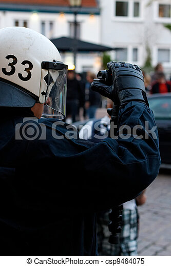 Police Officer Films Protesters - csp9464075