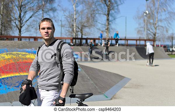 Portrait of BMX bicycle rider on urban skatepark background