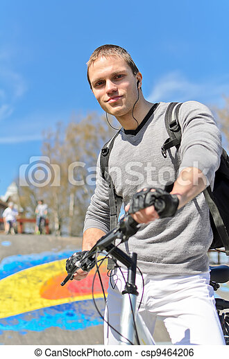 Portrait of BMX bicycle rider on urban skatepark background