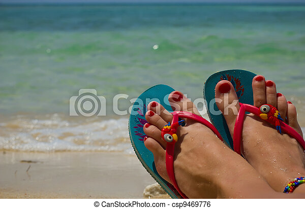 Colored flip-flops on the beach - csp9469776