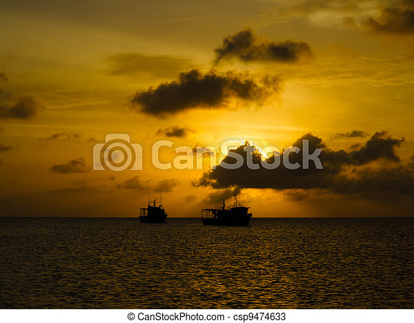 Silhouettes of fishing boats at sunset in Caribbean - csp9474633