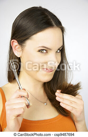 Girl with scissors ready to cut hair making weird face - csp9487694