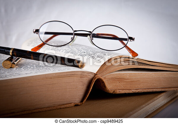 Glasses and pen laying on an old book - csp9489425