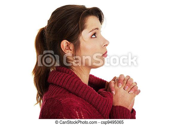 Closeup portrait of a young caucasian woman praying  - csp9495065