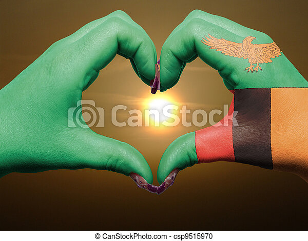 Tourist made gesture  by zambia flag colored hands showing symbol of heart and love during sunrise - csp9515970