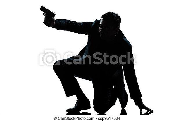 silhouette man kneeling aiming gun - csp9517584