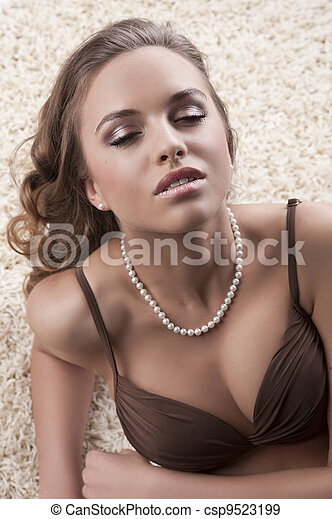 young alluring brunette in bra over carpet - csp9523199