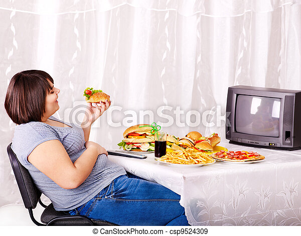 Woman eating fast food and watching TV. - csp9524309