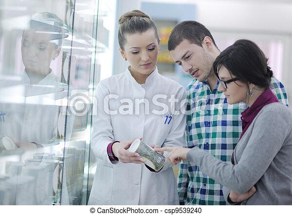 pharmacist suggesting medical drug to buyer in pharmacy drugstore - csp9539240
