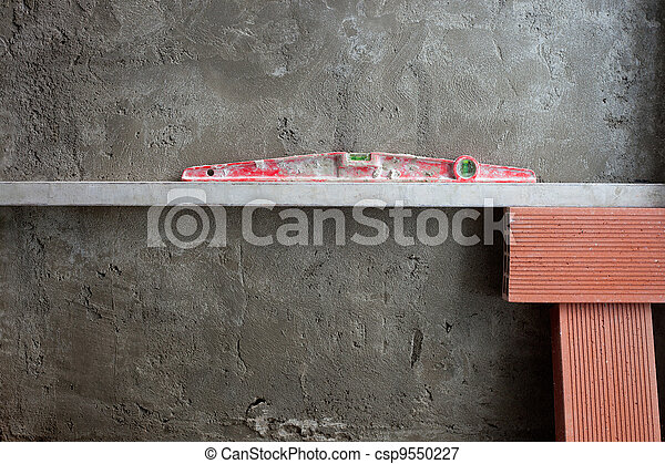 bubble spirit level tool in red on costruction cement - csp9550227