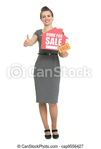 Smiling realtor showing thumbs up and home for sale sold sign - csp9556427